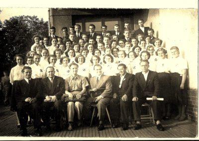 """12. Chór """"Harmonia"""" z dyrygentem p. Smołuchą. Zdj. wykonane przy Szkole Podstawowej w 1953 roku. Fotografia ze zbiorów p. Tubackiej."""